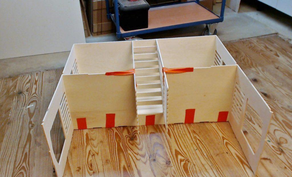 """J'ai couche l'""""embryon"""" de maison sur le dos, c'est la position le plus pratique pour guider l'escalier bien droit au fond de son logement. Je mets des adhésifs de chaque coté pour les serrer contre le plancher de l'étage1"""